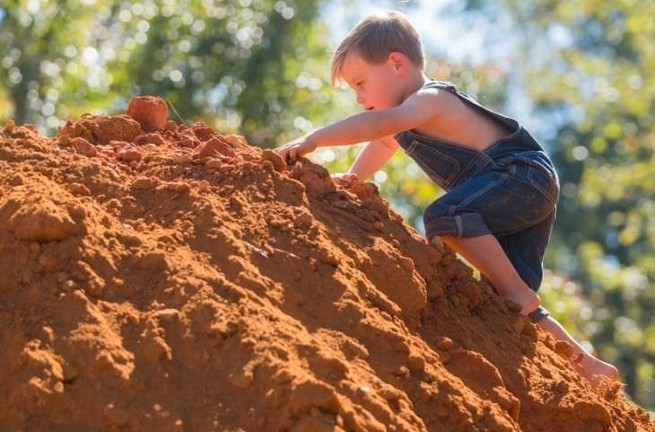 מחקר על משחק של ילדים באדמה ולכלוך: ילד מטפס על תל אדמה
