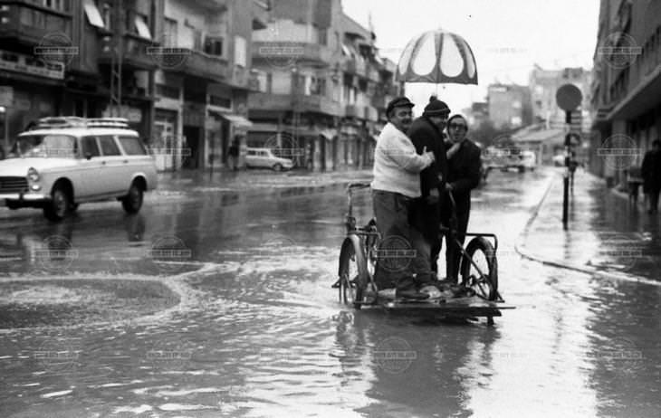 תמונות נוסטלגיות של תל אביב: בשל הצפות בדרך שלמה פינת רחוב אבולעפיה, אנשים חוצים את הכביש בעזרת עגלת הובלה; שנת 1974.