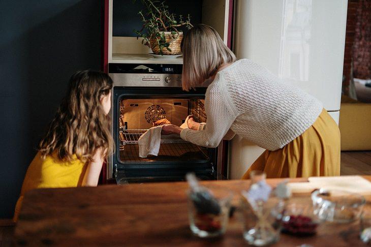 שאלות וניסויים מדעיים לילדים: אימא ובת מכניסות משהו לתנור אפייה