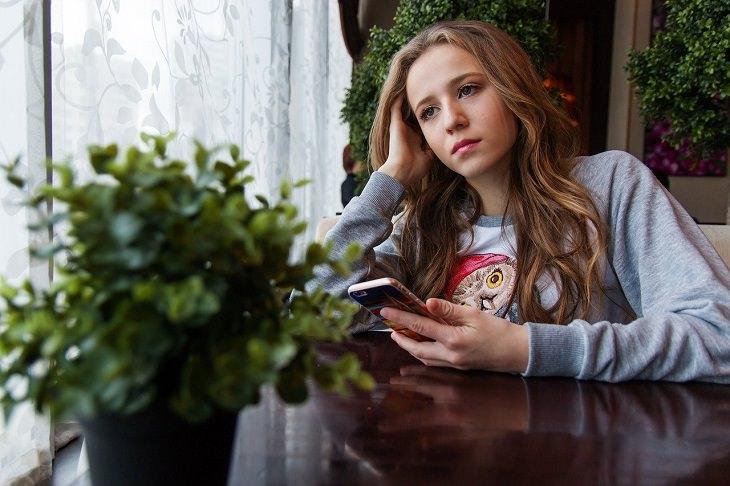 התמודדות עם מניפולציות: בחורה עצובה מחזיקה סמארטפון וחושבת