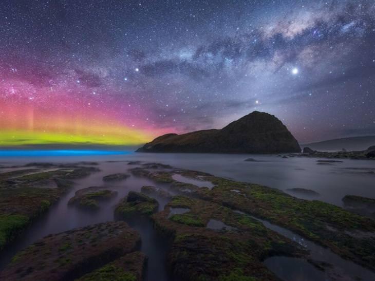 תחרות צלם זוהר הקוטב 2020: אי הררי וים עם סלעים ירוקים, וברקע זוהר הקוטב בגוונים שונים