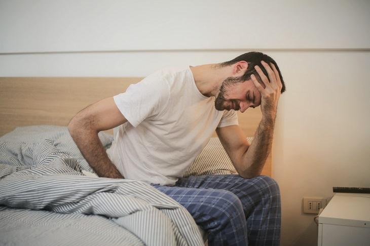 סיבות לישון ללא כרית: בחור יושב על מיטה ומחזיק את ראשו