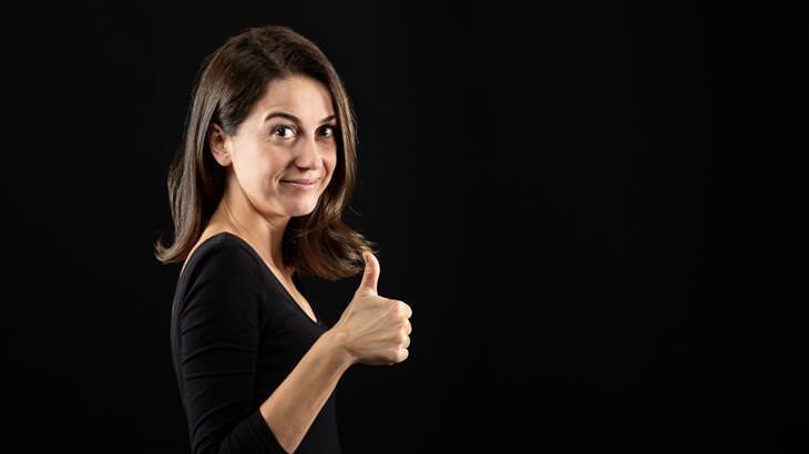 התנהגויות שמעידות על חוסר ביטחון עצמי: אישה עם חצי חיוך מסמנת לייק עם האצבע