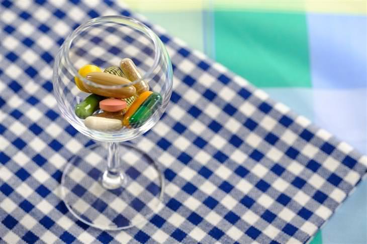 דברים שצריך לברר לפני שנוטלים תרופות: טבליות בתוך כוס יין