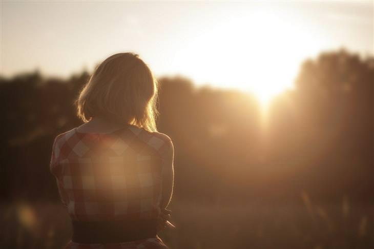 טיפים לשלום בית בעזרת קשיבות: אישה עומדת מול עצים שמאחוריהם שוקעת השמש