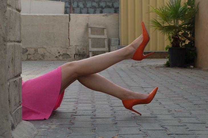 טיפול ברגליים עייפות: רגליים של אישה שלובשת חצאית ורודה ונעלי עקב אדומות