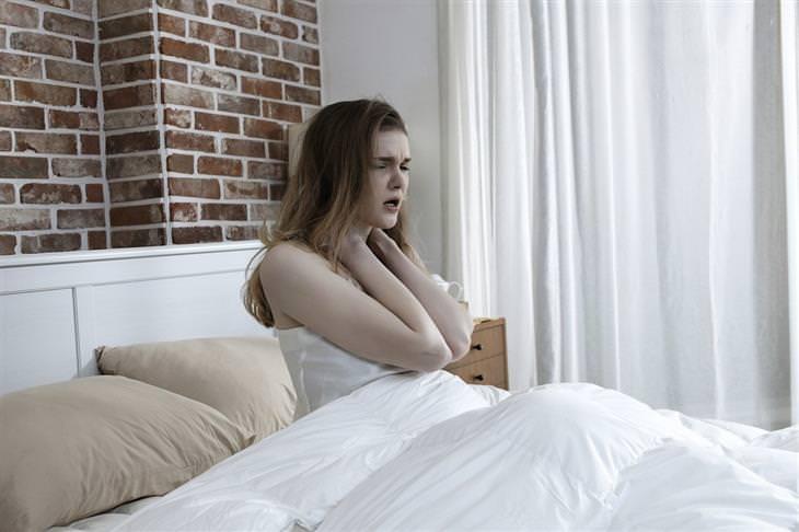 סיבות לערפול מוחי: אישה במיטה תופסת את צווארה בידיה