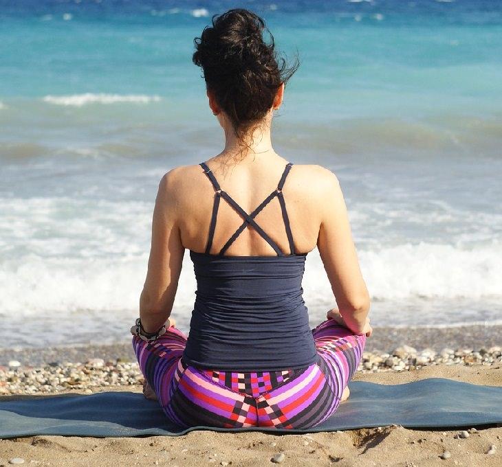 היתרונות של תנוחות היוגה: אישה מתרגלת יוגה מול הים
