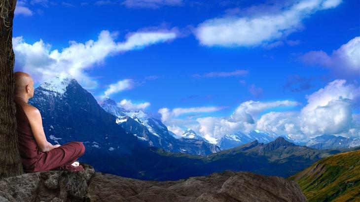 עצות מנזיר כיצד להשלים עם מחשבות מעיקות: נזיר יושב על צוק ומסתכל על נוף הררי