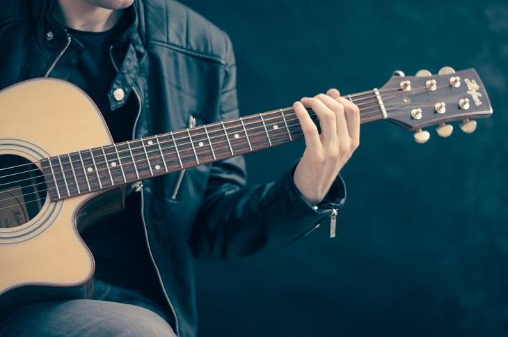 יתרונות של נגינה: בחור מנגן על גיטרה