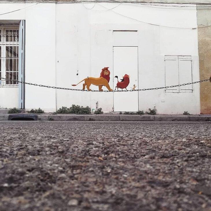 אמנות רחוב של דמויות מצוירות מפורסמות: סימבה, טימון ופומבה מתהלכים על שרשרת רחוב