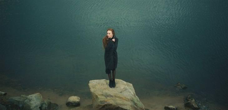 איך לדבר עם בן אדם בדיכאון: אישה עומדת על אבן מול ים
