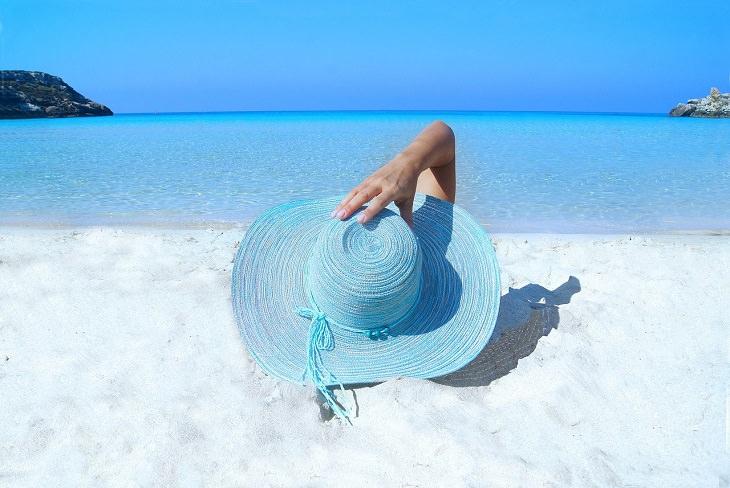 מחקרים על קוסמטיקה וטיפוח: אישה יושבת על חוף ים עם כובע
