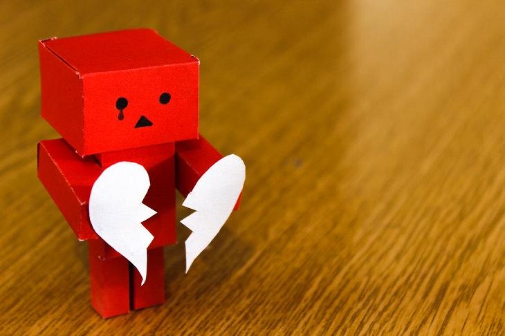 מטען רגשי: בובת קרטון אדומה עם ציור של דמעה מתחת לעין, מחזיקה לב שבור