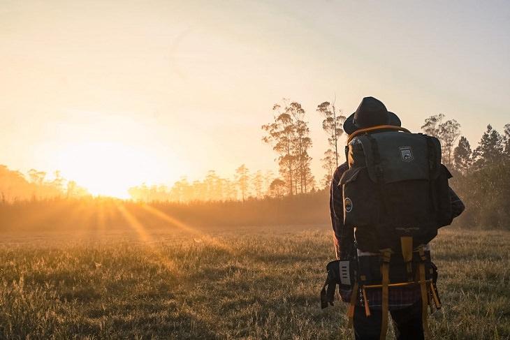 מטען רגשי: גבר נושא תרמיל כבד והולך בפארק