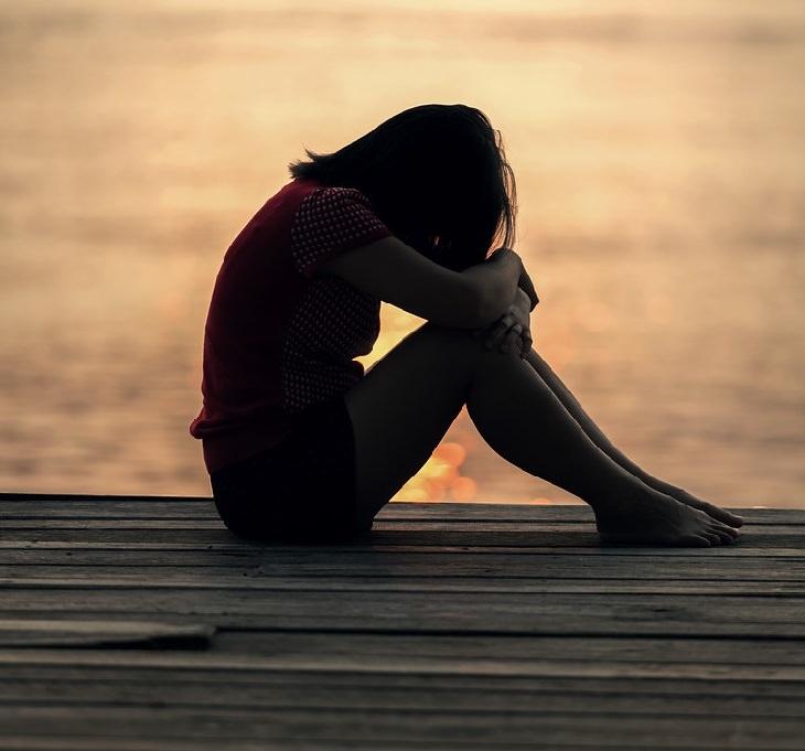 התנהגות מתבגרים: צעירה יושבת מול הים וראשה מושמט