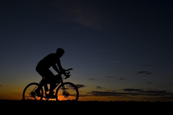 בדיחה על מהנדס בגיהינום: אדם רוכב על אופניים בשקיעה