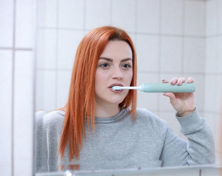 מאכלים ומשקאות מכתימים: אישה מצחצחת שיניים מול המראה