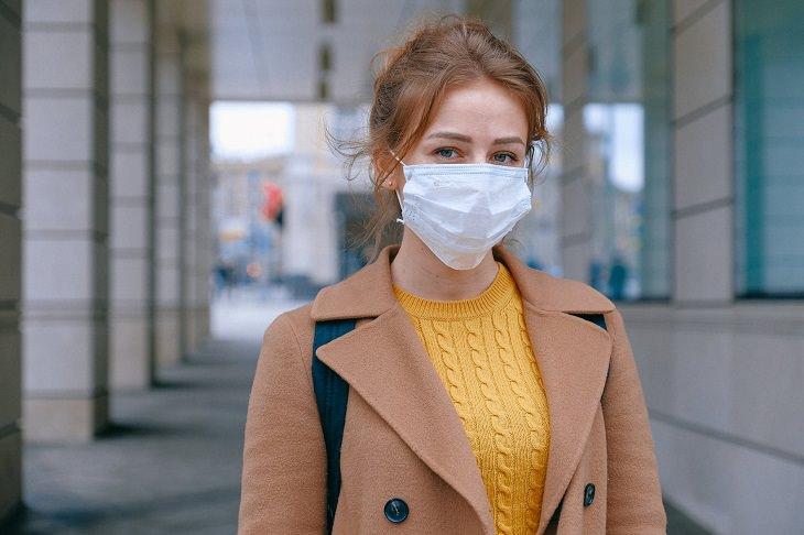 השפעת הספרדית מול הקורונה: אישה עם כיסוי על פיה ואפה