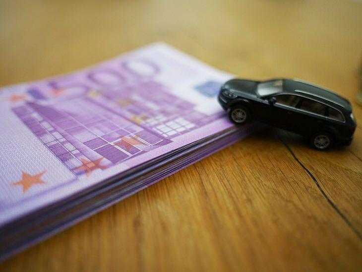 טיפים לשמירה על התקציב הביתי: מכונית צעצוע מונחית על ערמת שטרות
