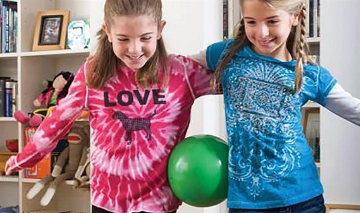 אימוני כושר שאפשר לעשות בבית: שתי ילדות עם כדור צמוד למותניהן