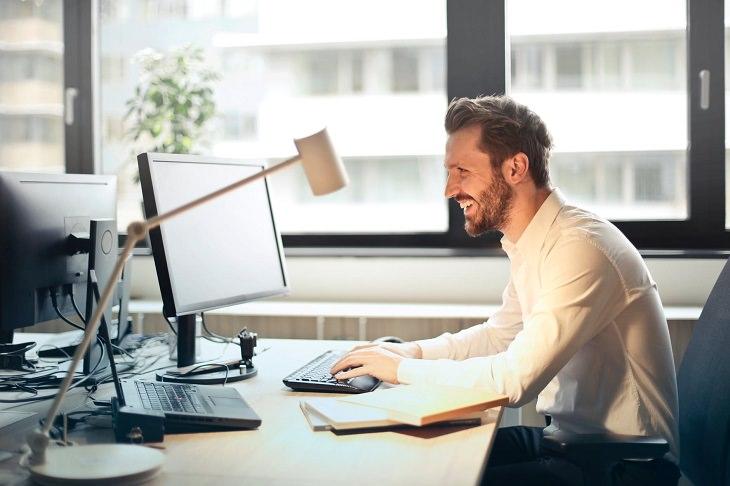 תסמונת ראיית מחשב: בחור יושב מול מסך מחשב ומחייך