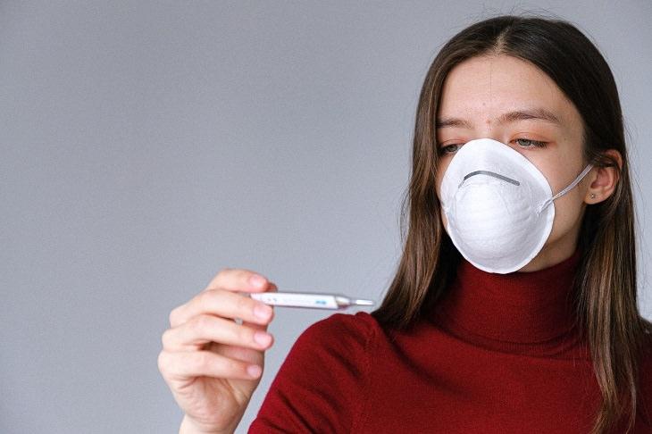 מחקר של מכון ויצמן אודות הקורונה: אישה עם כיסוי על הפה, מסתכלת על מד חום