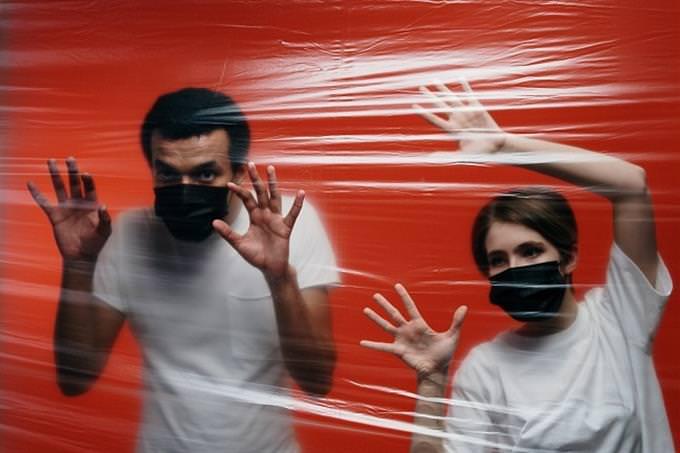 מה לעשות אחרי הסגר: זוג עם מסכות פנים עומד מאחורי יריעת ניילון