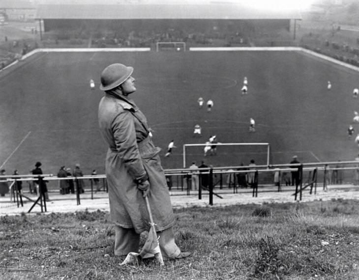תמונות היסטוריות: תצפיתן בריטי סורק את השמיים כדי להתריע מפני תקיפות של חיל האוויר הגרמני בזמן משחק כדורגל. שנת 1940.