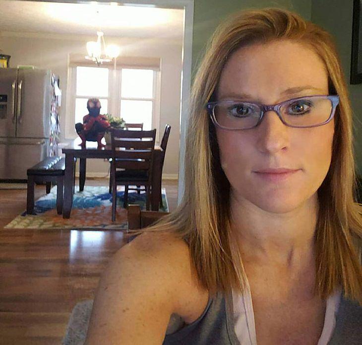 תמונות מצחיקות של הורים בבית עם ילדים קטנים: אימא מנסה לעבוד מהבית בזמן שהילד מטפס על השולחן בתחפושת של ספיידרמן