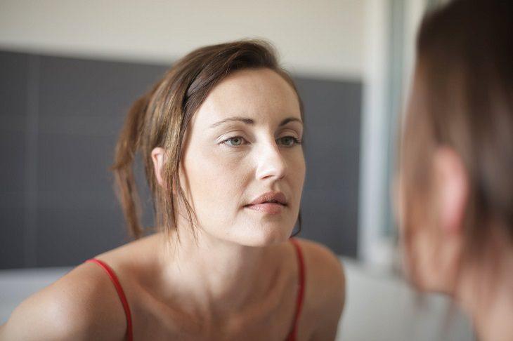 דימוי גוף חיובי: אישה מסתכלת על השתקפותה במראה