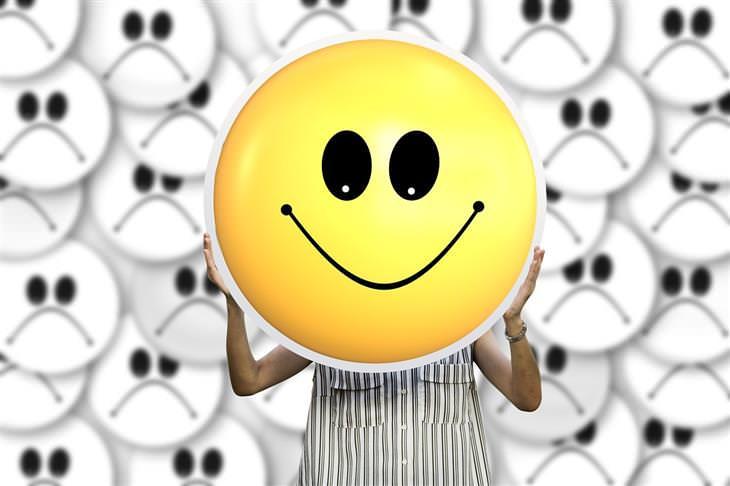 חיוביות רעילה: אישה מחזיקה מול פניה פרצוף מחייך ומאחוריה פרצופים עצובים
