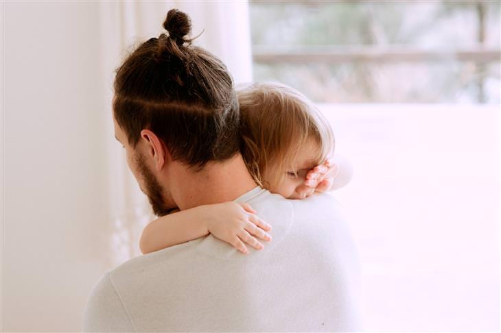 איך להתמודד עם כעס על הילדים: אבא מחבק את בתו שבוכה