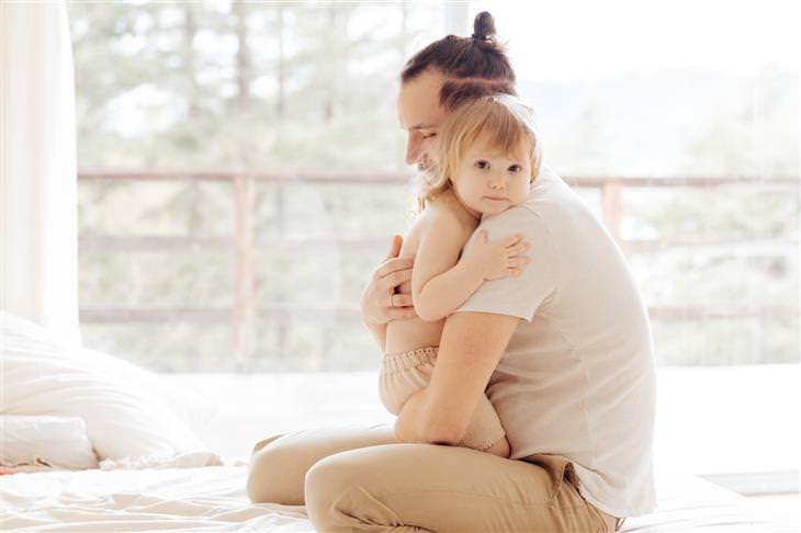 איך להתמודד עם כעס על הילדים: אבא מחבק את בתו התינוקת