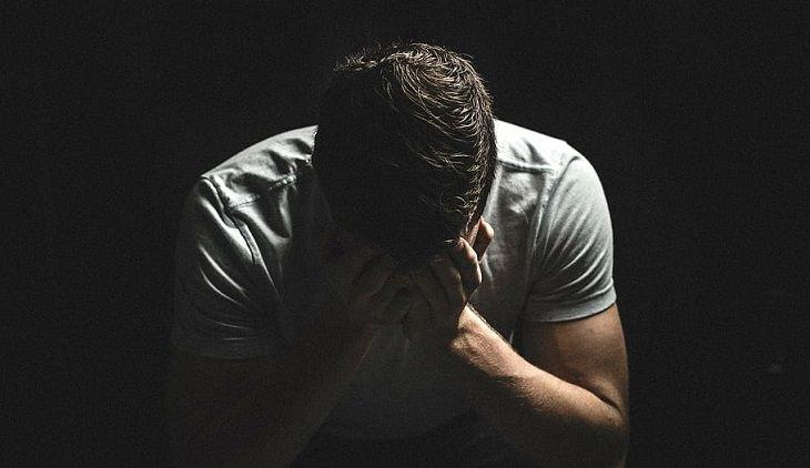 איך להיפטר ממחשבות שליליות: גבר מחזיק את ראשו בדיכאון