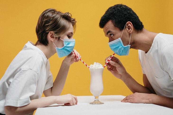 זוגיות בתקופת הקורונה: זוג חבוש במסכות פנים שותה מילקשייק