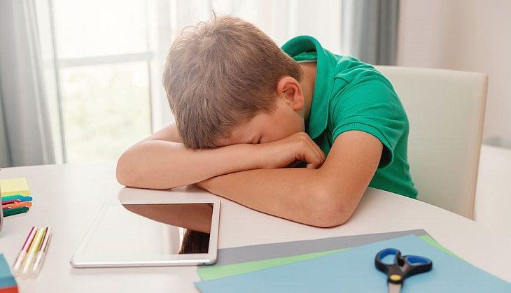 עצות להורים על למידה מהבית: ילד משועמם ליד שולחן עם דפי עבודה וטאבלט
