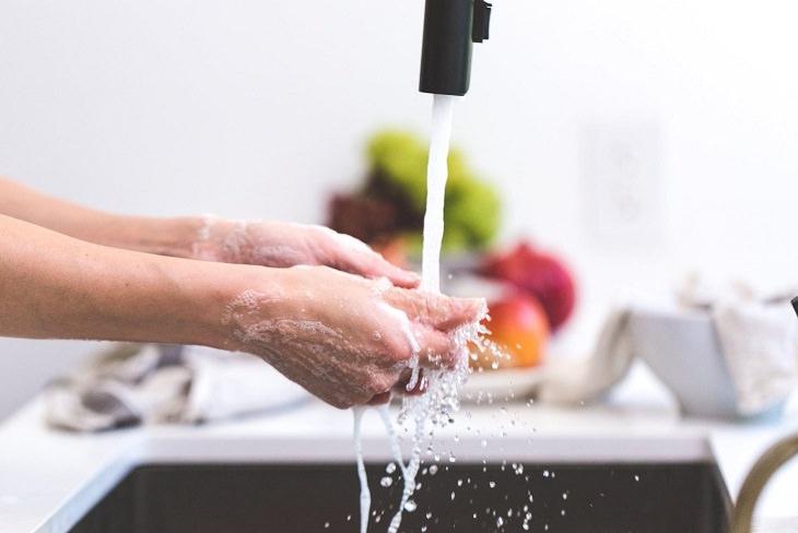 משטחים שצריך לנקות מנגיף הקורונה: אדם שוטף ידיים מתחת לברז