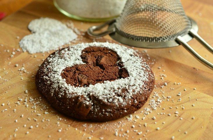 יתרונות בריאותיים של שמיר: עוגיית שוקולד שמפוזרת מעליה אבקת סוכר, ולצידה מסננת הפוכה
