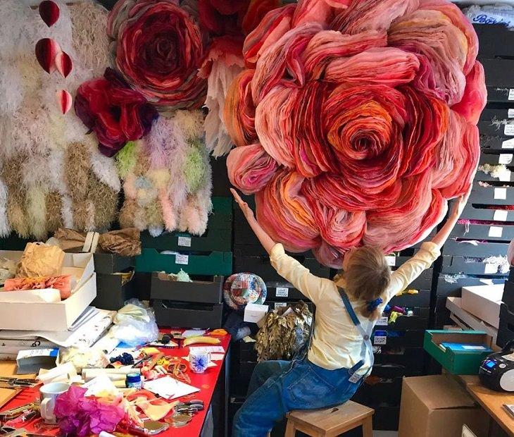 פרחי ענק מנייר טישו: האמנית בחדר העבודה שלה, מחבקת פרח ענקי