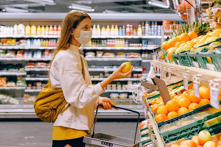 מסכת פנים נגד קורונה: בחורה עם מסכת פנים, בוחרת לימון בסופר