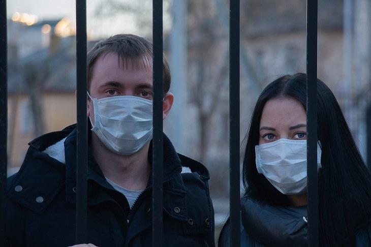הבדלים בהידבקות בקורונה בין גברים לנשים: אישה וגבר לבושים במסכת פנים מאחורי גדר