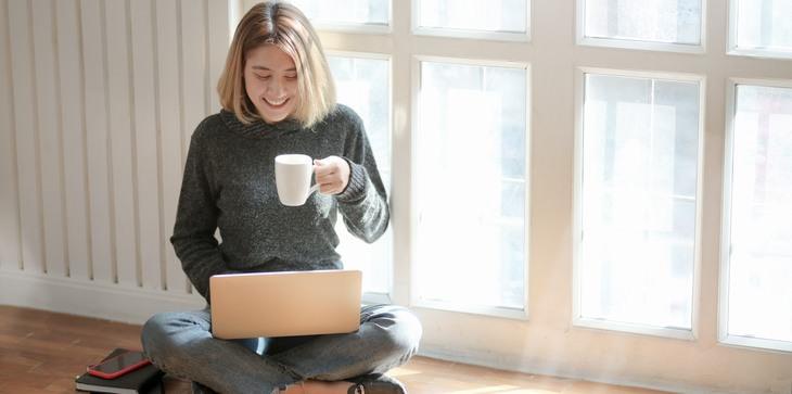שאלות שעליכם לשאול את עצמכם כשאתם בבית: אישה מחייכת למחשב עם כוס קפה ביד