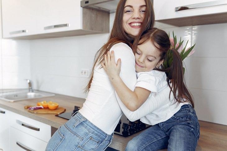 טיפים להורים לניהול למידה מרחוק: אימא ובת מתחבקות במטבח