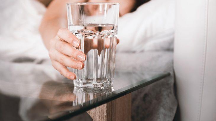 סיבות לא להשאיר כוס מים ליד המיטה לפני השינה: אישה מחזיקה כוס מים שעומדת על שידה ליד מיטתה