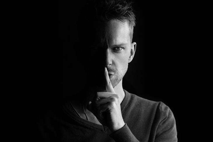איך לזהות מניפולציות רגשיות: איש משתיק עם אצבע מול הפה