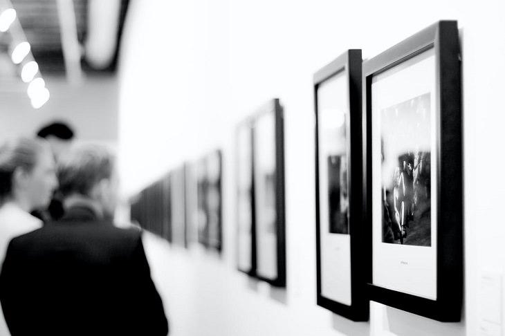 סיורים וירטואליים במוזיאונים בארץ: אנשים מסתכלים על תמונות בתערוכה