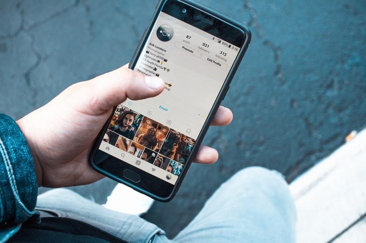 הקשר בין תחושת בדידות ורשתות חברתיות: יד מחזיקה סמארטפון עם אינסטגרם