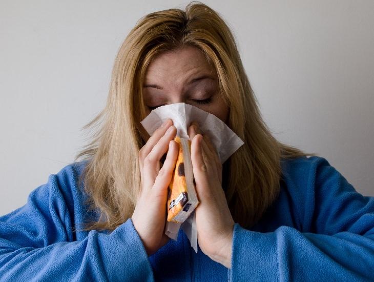יתרונות של כורכום וג'ינג'ר: אישה מקנחת את האף עם טישו