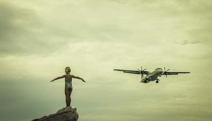 סיבות לחלום בגדול: ילדה על צוק מרימה ידיים לאוויר וברקע מטוס קטן